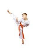 Idrottsman nen på en vit bakgrund i en kimono utför en hög slagfot Royaltyfria Foton