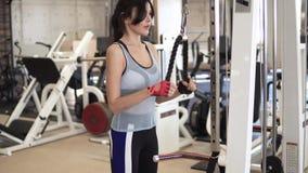 Idrottsman nen som gör övningar på tricepens på maskinen i idrottshallen flicka i sportswear på utbildning arkivfilmer