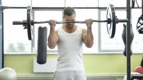 Idrottsman nen som gör övningen för biceps med skivstången Unga muskulösa mandrev på idrottshallen royaltyfri fotografi