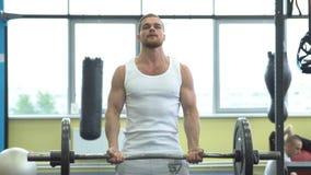 Idrottsman nen som gör övningen för biceps med skivstången Unga muskulösa mandrev på idrottshallen CrossFit utbildning arkivfilmer