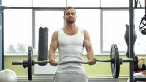 Idrottsman nen som gör övningen för biceps med skivstången Unga muskulösa mandrev på idrottshallen CrossFit utbildning royaltyfria bilder