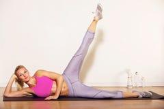 Idrottsman nen som gör henne ben som sträcker övning Arkivfoton