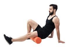 Idrottsman nen som masserar och sträcker, lägger benen på ryggen kalvmuskler med skumrullen arkivbild
