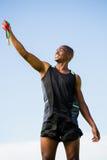 Idrottsman nen som poserar med guldmedaljen efter seger Royaltyfri Bild