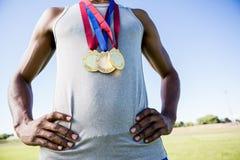 Idrottsman nen som poserar med guldmedaljer runt om hans hals arkivbilder