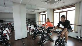 Idrottsman nen som två är förlovad på en stationär cykel i idrottshall lager videofilmer