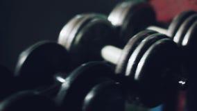 Idrottsman nen tar en hantel för utbildning Hantlar i idrottshall lager videofilmer
