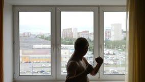 Idrottsman nen värmer upp under en ottagenomkörare i hem- rum inomhus stock video