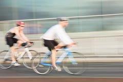 Idrottsman nenar som rider cyklar Arkivfoto