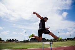 Idrottsman nenbanhoppning ovanför häcken Fotografering för Bildbyråer
