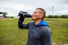 Idrottsman nendricksvatten från en flaska royaltyfri foto