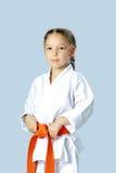 Idrottsman nenflicka i en kimono med det orange bältet Fotografering för Bildbyråer