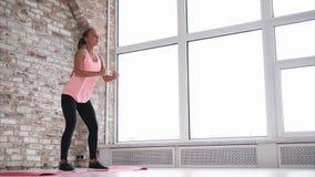 Idrottsman nenflickan gör squats i modern vindinre av sportklubban nära fönster lager videofilmer