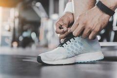 Idrottsman nenhänder som binder skosnöre i sportkorridor Arkivbild