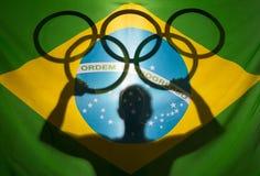 Idrottsman nenHolding Olympic Rings brasiliansk flagga Fotografering för Bildbyråer