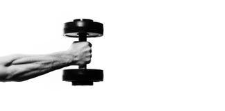 Idrottsman nenkroppsbyggare som in rymmer handen en hantel, muskulös handnolla arkivbild