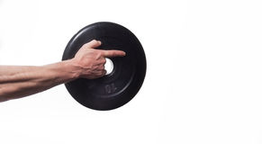 Idrottsman nenkroppsbyggare som in rymmer handen en skiva för hantlar, poin arkivfoto