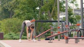 Idrottsman nenkvinnan som gör lutningar, övar, medan utomhus- utbildning i sommar parkerar lager videofilmer