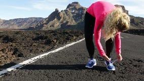 Idrottsman nenlöparekvinna som binder rinnande skor på körning lager videofilmer