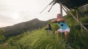 Idrottsman nenman och färdig kvinna som utbildar satt övning på tropisk bergbakgrund Utbildning för stund för squatting för sport lager videofilmer