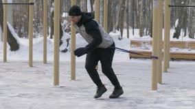 Idrottsman nenman som gör crossfitövning med expanderen på utomhus- vinterutbildning arkivbild