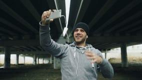 Idrottsman nenman som har video pratstund på smartphonen med hans instruktör efter genomkörare på stads- läge utomhus i vinter arkivfilmer
