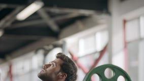 Idrottsman nenman som squatting med viktskivstången på bodybuildingutbildning i idrottshall lager videofilmer