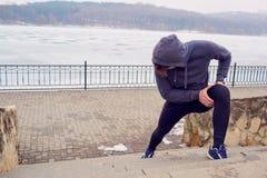 Idrottsman nenman som värmer upp, innan att köra Vinter för sportlivvår arkivfoto