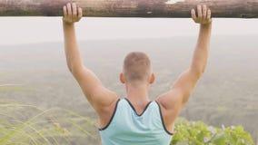 Idrottsman nenmanlyftande vikt vid träskivstången medan utomhus- utbildning Konditionman som gör pressövning med tung timmer lager videofilmer