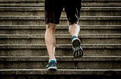 Idrottsman nenmannen med det starka benet tränga sig in den stads- stadstrappuppgången för utbildning och för spring i sportkondi