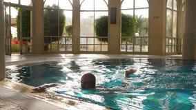 Idrottsman nenmansimning i pöl och som ut kommer från vatten i semesterorthotell stock video