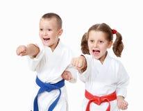 Idrottsman nenpojken och en flicka slår en stansmaskinarm på en vit bakgrund Arkivfoto