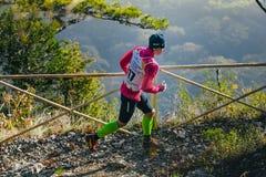 Idrottsman nenspring för ung kvinna på bergslinga i bakgrund av bergdalen Royaltyfri Fotografi