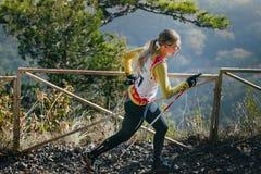 Idrottsman nenspring för ung kvinna på bergslinga med nordiska gå poler Royaltyfri Bild
