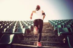 Idrottsman nenspring på trappa begrepp för wellness för genomkörare för kvinnakondition jogga Arkivbild
