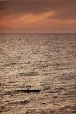 Idrottsman på kanoten på solnedgång Royaltyfri Foto