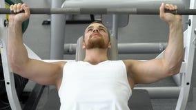 Idrottsman som gör skivstångbänken som trycker på, medan öva på konditionklubban Muskulös man som övar i idrottshallen arkivfoton