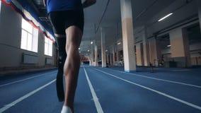 Idrottsman som joggar, bärande bionisk protes, tillbaka sikt lager videofilmer