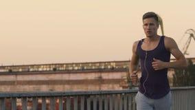 Idrottsman som joggar och att lyssna till favorit- musik som utbildar för konkurrens arkivfilmer