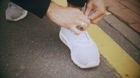 idrottsman som 4K binder skosnöre som förbereder sig att starta Kameralutande som panorerar upp idrottsman nenframsidan Förberede lager videofilmer