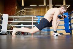 Idrottsman som sträcker ben i boxningsring Arkivbild