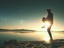Idrottsman som sträcker efter sport på havet på soluppgång i morgon Idrottsman nen som tillbaka böjer Arkivfoton