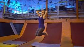 Idrottsmanbanhoppningen för ung kvinna på en trampolin i kondition parkerar och göra exersice inomhus lager videofilmer