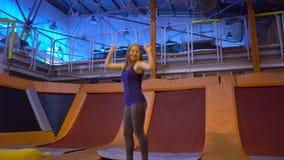 Idrottsmanbanhoppningen för ung kvinna på en trampolin i kondition parkerar och göra exersice inomhus arkivfilmer