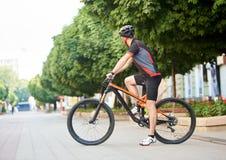 Idrottsmankorsning stadsgata på cykeln royaltyfri fotografi