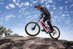 Idrottsmannen i sportswear på en mountainbike rider på stenarna Royaltyfri Fotografi