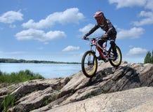 Idrottsmannen i sportswear på en mountainbike rider på stenarna Royaltyfria Foton