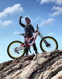 Idrottsmannen i sportswear på en mountainbike rider på stenarna Arkivfoto
