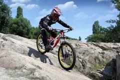 Idrottsmannen i sportswear på en mountainbike rider på stenarna Royaltyfria Bilder