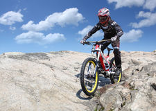 Idrottsmannen i sportswear på en mountainbike rider på stenarna royaltyfri foto